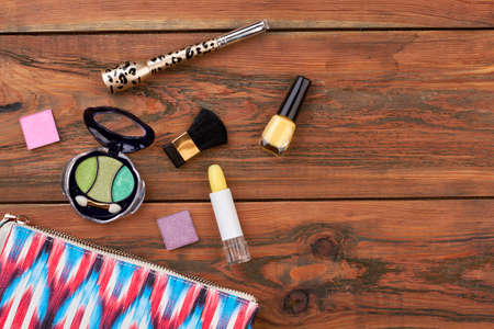 Wooden background with cosmetics. Pink toiletry bag and different cosmetics products on brown background. Female makeup table.