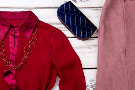 Female elegant clothes and accessories. Women red shirt, pink skirt and blue purse on wooden background.