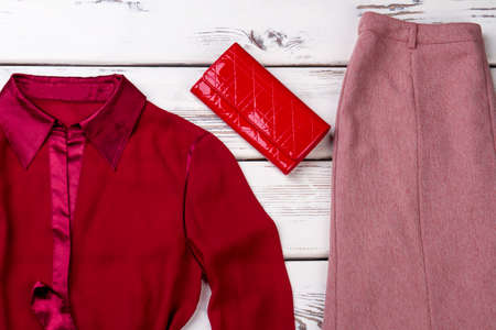 Female classic clothes and red purse. Feminine red shirt, skirt and leather wallet on white wooden background. Banque d'images