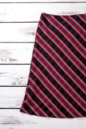 Classic red striped skirt. Female colorful skirt on white wooden background. Feminine fashion outfit.