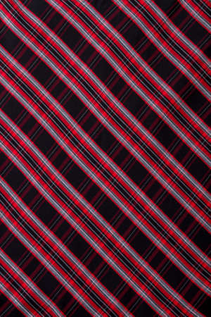 Black and red striped background. Black fabric with red stripes as wallpaper. Female skirt close up.