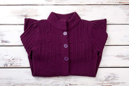 Warm purple sweater for women. Female knitted cardigan folded on white wooden background. Feminine autumn outfit.