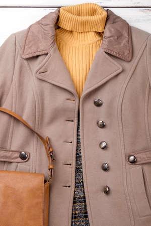 Female overcoat, sweater and handbag. Women autumn modern outfit. Feminine fashion look. Stock Photo