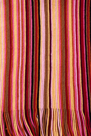 Striped multicolored scarf close up. Knitting texture of colored knitted fabric. Detail of female winter garment.