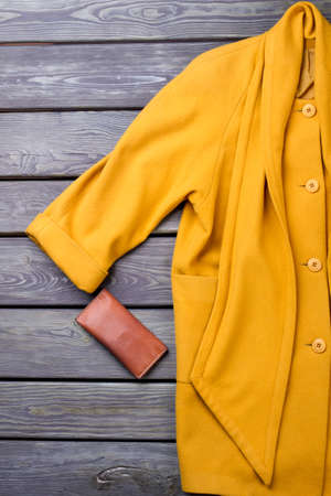 Female luxury yellow overcoat. Women fashion cashmere topcoat and leather purse on old wooden background. Stock Photo