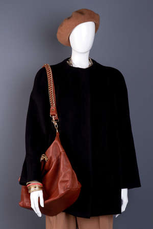 Female mannequin with stylish brown handbag. Dummy in women black and brown autumn outfit. Feminine fashion and style.