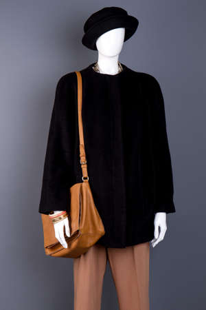 Female mannequin with leather fashion handbag. Brown trousers, black coat and hat on women mannequin. Autumn fashion garment and accessories.