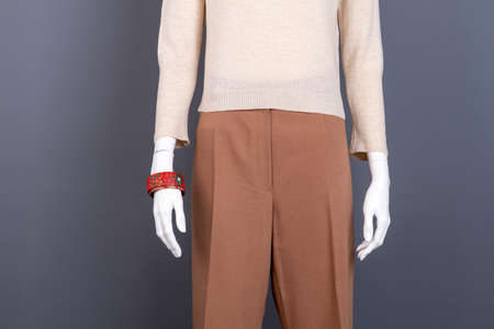 Beige sweater and brown trousers on mannequin. Female simple design apparel and accessories. Women garment in mall. Stock Photo