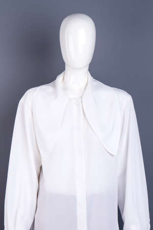 Long sleeve white shirt for ladies. Brand chiffon women blouse on mannequin. Feminine high quality apparel. Stock Photo