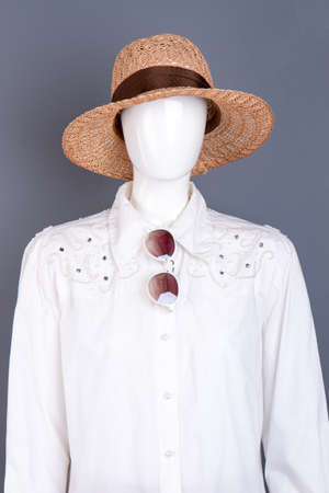 Straw hat and fashion design female blouse. Female mannequin wearing white shirt, sunglasses and woven hat, grey background. Ladies glamour and elegance.