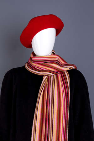 Red beret, scarf and black overcoat. Mannequin wearing red women headgear, colorful scarf and coat. New collection of autumn clothes for women. Stock Photo