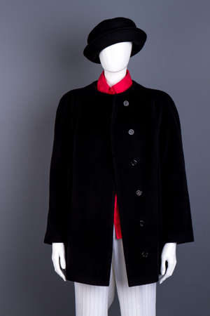 Female mannequin wearing black hat and coat. Buttoned overcoat for women. Ladies classy clothes and accessories.