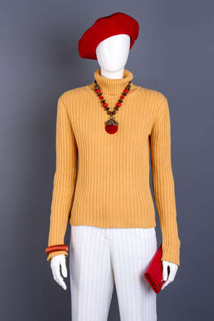 Red beret and accessories on mannequin. Women sweater, trousers and red color accessories. Women fashion look.