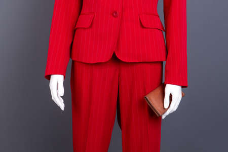 Female elegant suit and leather wallet. Manneqin in female red blazer and pants, cropped image. Fashion design outfit for ladies.
