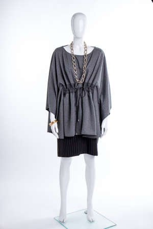 Female mannequin in extravagant grey tunic. Women fashion blouse, skirt and jewelry on female mannequin. Ladies stylish outfit.