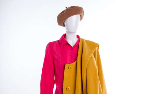 Red blouse and yellow coat on mannequin. Beret, shirt and overcoat for ladies. Women autumn style.