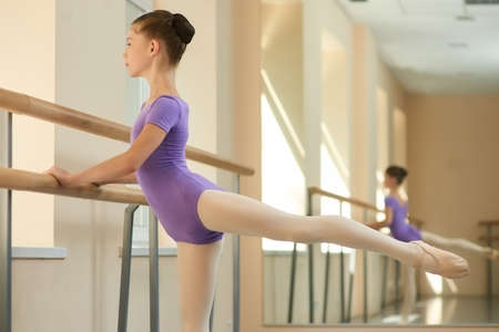 Young ballerina practice on barre. Girl stretching out on railing at ballet studio. Exercises of ballet-dancer before performance. Skill and talent of young ballerina. Stockfoto