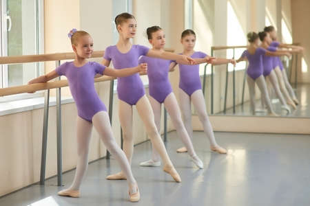 Young ballerinas having rehearsal at ballet school. Pretty young ballet dancers training at ballet barre in class.