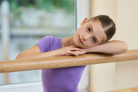 Lovely little ballerina, blurred background. Cute young girl resting head on her arms on ballet barre in studio. Little exhausted ballerina after hard ballet practice.
