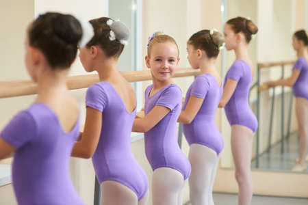 Young happy ballerina near ballet barre. Cute little ballet dancers practicing some dance element at a barre in a dance class. Professional school of ballet dance for kids. Banque d'images