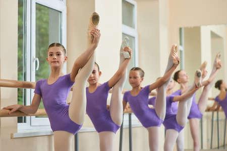 Le giovani gambe delle ballerine si sollevano in studio. Gruppo di giovani ballerine che tengono le gambe in estensione alla sbarra di balletto. Ragazze di balletto che hanno pratica.
