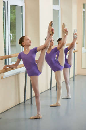 Three young ballerinas stretching legs. Young beautiful ballet girls training their legs stretch at ballet barre. School of professional ballet dance.