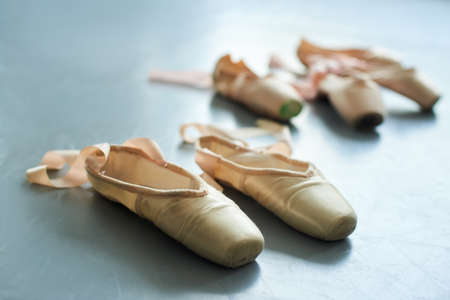 Close up old ballet pointe shoes. Traditional slippers for classical ballet dance on the floor. Female ballet dancer footwear.