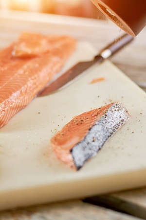 Raw salmon cooking process. Preparation of fresh salmon piece with spices. Raw salmon on cutting board.