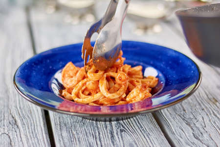 Kitchen stainless tongs putting pasta on plate. Appetizing spaghetti with red sauce and calamar on plate. Cooking of delicious italian dish.