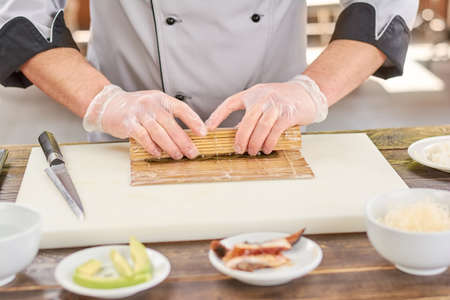 Cook making a sushi roll with bamboo mat. Chef sat professional kitchen preparing sushi. The process of sushi roll preparation. Foto de archivo