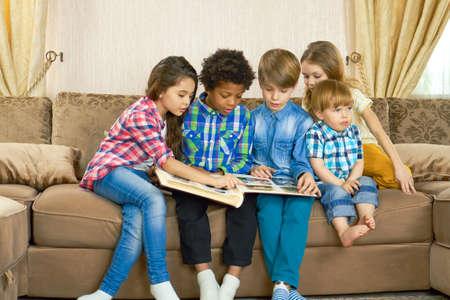 Children looking through photo album. Kids sitting on the sofa.