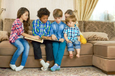Kids reading a book indoors. Children sitting in the room.