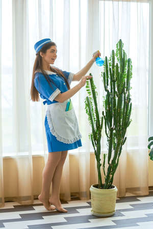 Young maid water spraying plant. Stock Photo