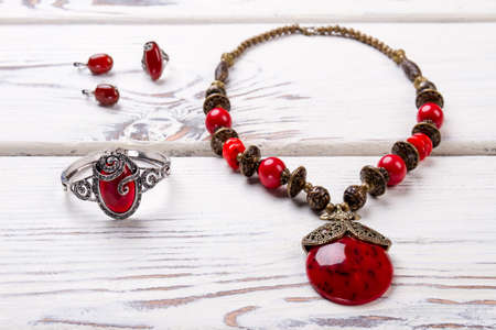 Close up jewelry necklace with bracelete and earrings. Red amulets, beautiful expensive accessories.