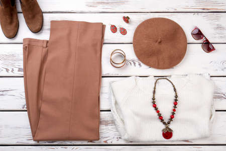 Womens dress with accessories. Folded brown pants, pair of shoes, brown hat, sunglasses and necklace with amulet on white woolen sweater.