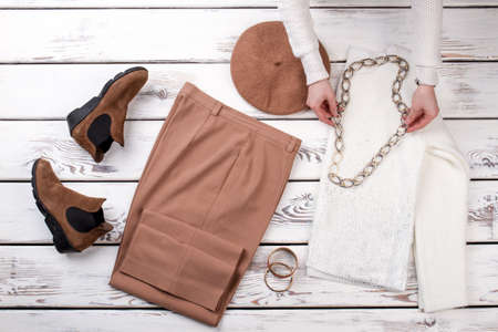 Female hands put on chain necklace on white woolen sweater. Brown womens shoes, trousers, hat, braceletes and white woolen sweater arrangement. Imagens