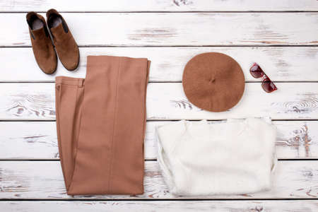 Concept of womens clothes are laid out on the table. Folded brown trousers and white woolen sweater.