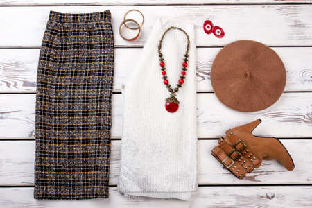 Layout womens outfit with accessories. Casual and elegant, checkered trousers, high heels shoe, white sweater, hat, necklace, bracelete, earring.