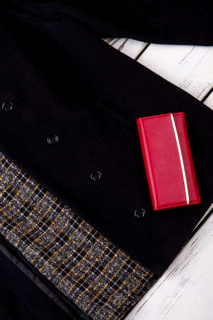 Close up red wallet on black coat. Cashmere jacket with red leather purse.