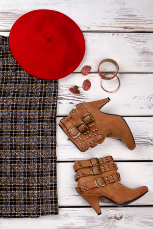 Women garments for stylish winter outfit. Trusers, shoes, hat and accessories on wooden showcase at shopping centre.