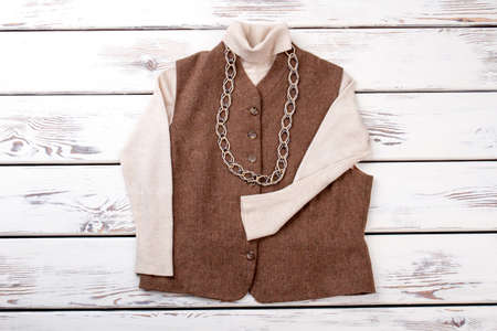 Brown sleeveless jacket with necklace. Bright beige white wooden desks surface background. Banco de Imagens