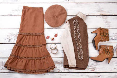 Autumn collection of women outfit. Full set of women clothes. Chain necklace, earring, bracelete. Brown heel boots with clasps.