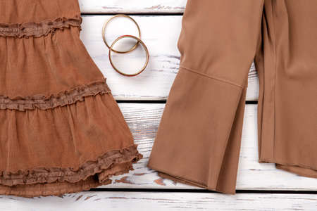 Close up parts of brown clothes. Two gold bracelets. Imagens