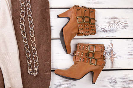 Pair of brown heel boots with clasps. Autumn jacket with chain necklace. White wooden desks surface background.