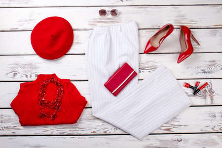 Casual fashionable womans appeal on white wood background. Red and white clothing and accessories. Фото со стока
