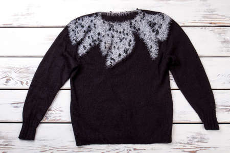 Decorated black sweater. Flat lay, top view. White wooden desk background.