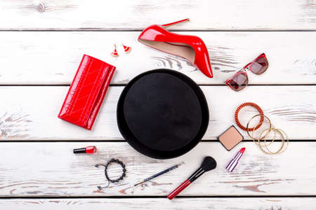 Clothing and fashion accessories. Black hat, red leather shiny wallet and high heel shoe. Cosmetic accessories for makeup.