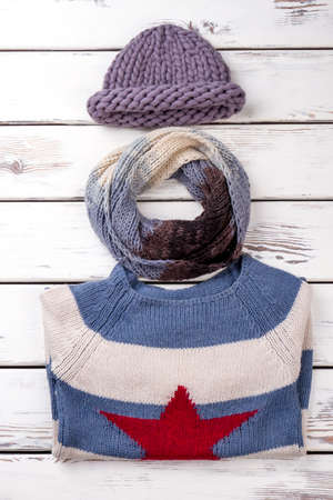 Knitted winter clothing. Folded winter sweater, scarf and hat, flat lay. Stock Photo