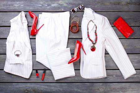 Layout of whte suit and red accessories. Grey wooden surface background.