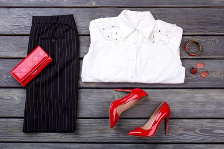Set of business clothes and accessories for woman on dark background. Black trousers, white shirt, red wallet and shoes.